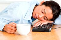 Beautiful woman sleeping on a keyboard while holding a cup of coffee at the office