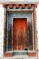 a worn out red wooden door at wangdichholing palace, bumthang district bhutan