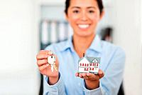 Attractive woman holding keys and a miniature house while looking at the camera at the office