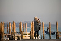 A woman taking a photo of the Grand Canal, Venice, Italy