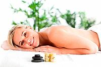 Smiling blonde woman lying on a lounger with stones and candles in a wellness center