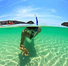 a young man snorkels holding a starfish underwater and another person paddling a boat, la paz baja california sur mexico