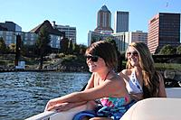 two teenage girls in bathing suits riding in a boat with the city in the background, portland oregon united states of america