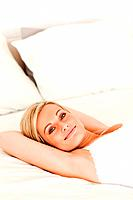 Portrait of a cute woman lying down on her bed