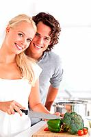 Portrait of a beautiful couple cooking while looking at the camera