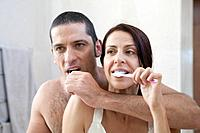 Couple brushing their teeth in bathroom