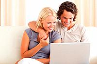 Smiling young couple using a laptop in their living room