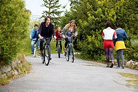 Teenagers riding bicycles in park