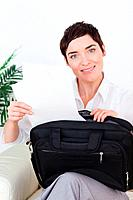 Smiling businesswoman putting some papers in her bag in a waiting room