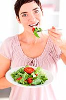 Woman eating salad in a kitchen
