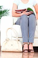 Part of a cute Woman on a sofa with a bag and a magazine in a waiting room