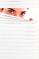 Businesswoman peeking through a venetian blind in an office