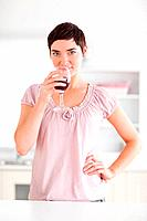Woman drinking a glass of wine looking into the camera in a kitchen