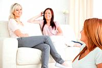 Goodlooking young woman separated from the others in a living room
