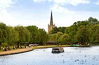 England, Warwickshire, Stratford_upon_Avon. Tourists enjoying a trip on a pleasure boat on the River Avon. The steeple of the Church of the Holy Trini...