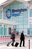 England, West Midlands, Birmingham. Businessmen crossing a zebra crossing with their baggage outside Birmingham Airport.