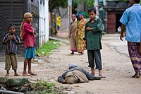 Children Standing Around A Man Laying On The Ground In The Slums, Sylhet, Bangladesh