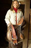 Woman Carrying Saddle
