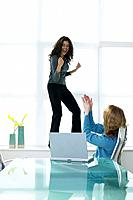 Cheering woman standing on windowsill applauded by colleague