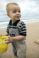 Boy on Beach with Yellow Bucket