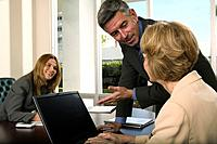 Business people in conference room, woman and man at laptop