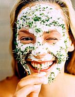 Woman with face mask closing one eye