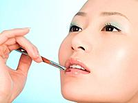 Chinese woman applying lip gloss