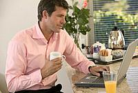 Man Having Breakfast and Working on Laptop in Kitchen