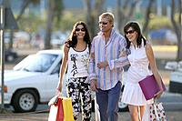 Man and Two Women Carrying Shopping Bags