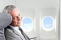 Germany, Bavaria, Munich, Senior businessman sleeping in business class airplane cabin