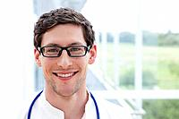 Germany, Bavaria, Diessen am Ammersee, Close up of young doctor with stethoscope, smiling, portrait