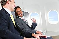 Germany, Bavaria, Munich, Businessmen talking in business class airplane cabin