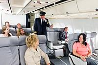 Germany, Bavaria, Munich, Flight captain saluting passengers in business class airplane cabin, smiling