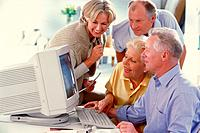 Four seniors in front of a computer