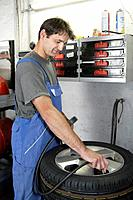 Germany, Ebenhausen, Mechatronic technician working on tyre in car garage