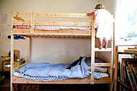 Little girl climbing up to top bunk
