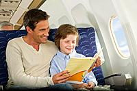 Germany, Munich, Bavaria, Man and boy reading book in economy class airliner