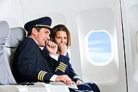 Germany, Bavaria, Munich, Mid adult flight personnels in business class airplane cabin, talking