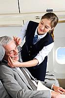 Germany, Bavaria, Munich, Young stewardess taking care of senior businessman in business class airplane cabin