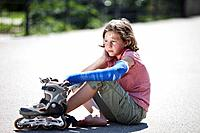 Germany, Bavaria, Wounded girl sitting on road after inline_skating accident