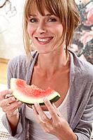 Young woman sitting on bed and holding watermelon slice in morning, smiling, close up, portrait