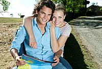 Italy, Tuscany, Young couple sitting with map at roadside