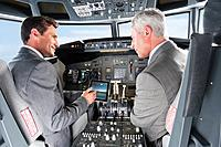 Germany, Bavaria, Munich, Businessmen showing digital table in airplane cockpit