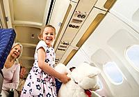 Germany, Munich, Bavaria, Women sitting and girl holding teddy bear in economy class airliner