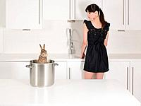 Woman looking at a rabbit in a saucepan