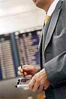 Businessman at Airport Using PDA