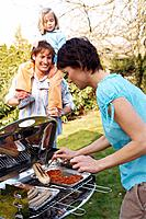 Parents with Daughter Having Barbecue in Yard