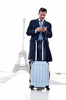 Businessman standing with luggage using a mobile phone with the Eiffel Tower in the background, Paris, Ile_de_France, France