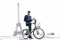 Businessman holding a newspaper and a mobile on a bicycle with the Eiffel Tower in the background, Paris, Ile_de_France, France