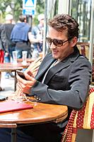 Man using a mobile phone in a restaurant, Paris, Ile_de_France, France
